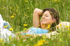 Young woman lying in meadow - stock photo