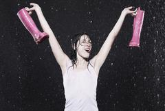 Woman holding rubber boots, arms up. Stock Photos