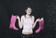 Woman holding rubber boots, clenching teeth. Stock Photos