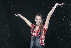 Girl standing in rain, arms up, smiling. Stock Photos