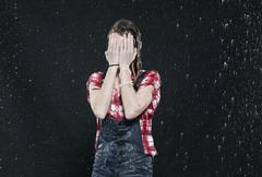 Girl standing in rain, covering face. - stock photo