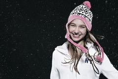 Girl wearing woolly hat in rain, smiling. Stock Photos