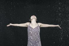 Woman enjoying in rain, arms outstretched. Stock Photos