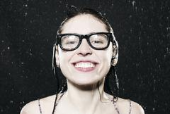 Woman with spectacles in rain, smiling. - stock photo
