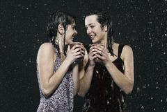 Friends standing in rain, holding disposable cup. Stock Photos