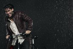 Man with bicycle in rain, smiling. Stock Photos