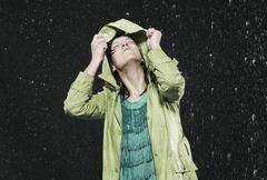 Woman holding hood in rain, looking up. - stock photo