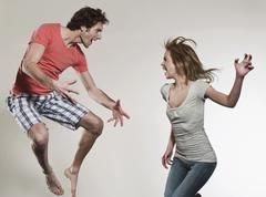 Stock Photo of Man and woman shouting and jumping against gray background