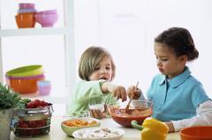 Stock Photo of Children (4-7) preparing sauce, close-up