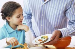 Stock Photo of Father showing decorated slice of bread to daughter (4-7), close-up