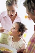 Mother feeding daughter (6-7) spaghetti - stock photo