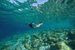 Croatia, Girl (10-11) snorkeling, rear view - stock photo