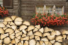 Switzerland, Stack of logs in front of block house Stock Photos