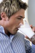 Young man drinking glas of milk - stock photo