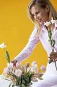 Stock Photo of Young woman arranging flowers in vase
