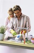 Young couple, man washing plate Stock Photos