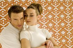 Young couple against wall paper, portrait - stock photo