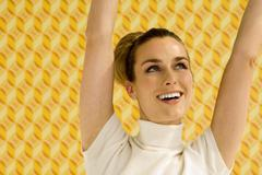 Young woman against wall paper, portrait - stock photo