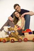 Young couple sitting on floor with toys Stock Photos