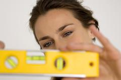 Young woman holding spirit level, close-up Stock Photos