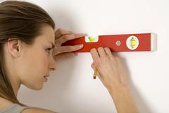 Young woman using spirit level, marking wall with pencil, smiling - stock photo