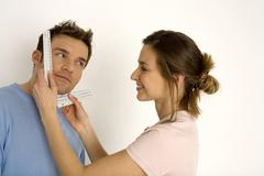 Stock Photo of Woman measuring man's face with ruler, smiling, close-up