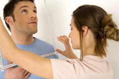 Woman measuring man's face with ruler, close-up Stock Photos