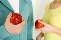 Man and woman holding apple, mid section, close-up Stock Photos