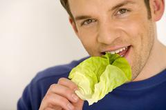 Young man eating lettuce leaf, close-up - stock photo