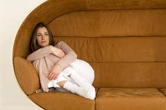 Young woman relaxing on sofa, looking away, close-up Stock Photos