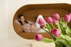 Young woman relaxing on sofa, focus on tulips in foreground Stock Photos