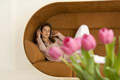 Woman relaxing on sofa with head phones, pink tulips in foreground Stock Photos