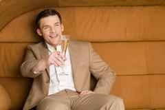 Man sitting on sofa holding out champagne glass, smiling - stock photo