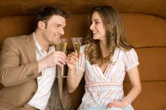 Young couple on sofa holding champagne glasses, smiling - stock photo