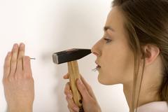 Woman hammering nail into wall, close-up, profile Stock Photos