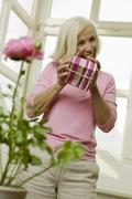 Stock Photo of Senior woman holding gift box, smiling, low angle view