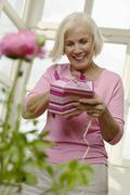 Senior woman opening gift box, low angle view, smiling - stock photo