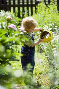 Boy (4-5) with watering can, portrait Stock Photos