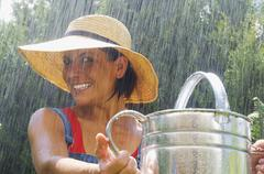 Stock Photo of Young woman with straw hat in the rain, portrait