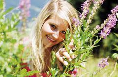 Stock Photo of Blond woman among flowers, portrait