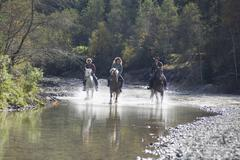 Austria, Salzburger Land, Altenmarkt, Young people riding horses across river - stock photo