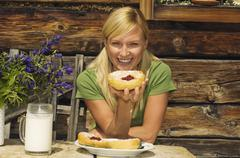 Austria, Salzburger Land, blonde woman drinking milk, eating pastries - stock photo