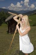 Austria, Salzburger Land, Altenmarkt-Zauchensee, Young woman with hayfork Stock Photos