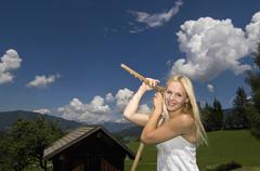 Austria, Salzburger Land, Altenmarkt-Zauchensee, Young woman with hayfork - stock photo