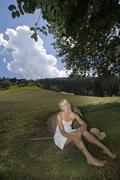 Austria, Salzburger Land, Altenmarkt-Zauchensee, Young woman sitting on meadow - stock photo