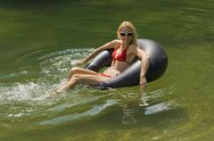 Austria, Salzburger Land, Lake Reitecksee, Young woman relaxing on floating tire Stock Photos