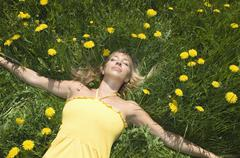 Austria, Salzburger Land, Young woman relaxing in meadow, eyes closed - stock photo