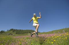Austria, Salzburger Land, Young woman running across meadow - stock photo