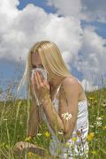 Austria, Salzburger Land, Altenmarkt, Young woman sneezing in meadow, portrait - stock photo