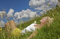 Austria, Salzburger Land, Altenmarkt, Young woman lying in meadow, eyes closed, Stock Photos
